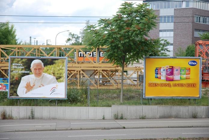 links Werbung für den Papstbesuch, rechts Ritex-Werbung
